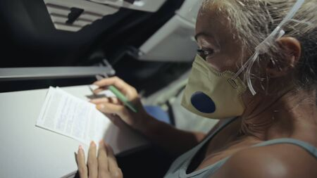 Woman travel caucasian at plane with wearing protective medical mask. Girl tourist at aircraft with protect respirator, fill out a registration form about her health. Coronavirus sars-cov-2 covid-19.