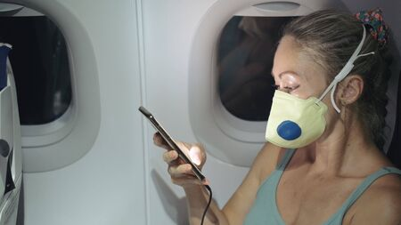 Woman travel tourist caucasian at plane aircraft with wearing protective medical mask. Read shock news about coronovirus at smartphone mobile. Virus coronavirus epidemic sars-cov-2 covid-19 2019-ncov.