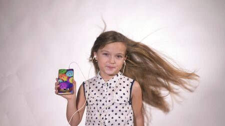 Child with earflaps dancing at studio background. The girl listens to music on the smartphone. The kid has loose long hair. Beautiful cute happy little girl listens to music on Headphones. Archivio Fotografico
