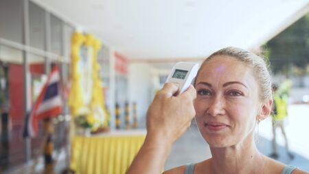Temperature check at a supermarket of woman, grocery store with thermal imaging camera installed. Image monitoring scanner to monitor the body temp of visitor customer girl. Coronavirus Covid-19. Standard-Bild