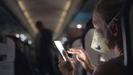 Woman travel tourist caucasian at plane aircraft with wearing protective medical mask. Read shock news about coronovirus at smartphone mobile. Virus coronavirus epidemic sars-cov-2 covid-19 2019-ncov. Standard-Bild - 143957286