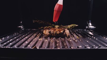 Delicious juicy meat steak cooking on grill. Silicone cooking brush. Aged prime rare roast grilling fresh marble tenderness beef. Prime beef fry on electric roaster, rosemary black pepper oil. 写真素材