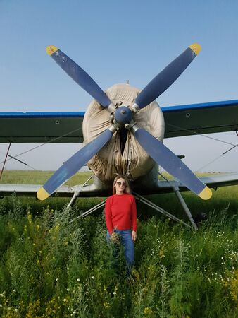 Woman portrait in front of an old aircraft. Young beautiful woman with red jacket stand in front of older bomber aircraft with a propeller in background. Photo shoot near the plane.