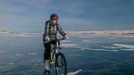 Woman is riding bicycle on the ice. Girl is dressed in a silvery down jacket, cycling backpack and helmet. Ice of the frozen Lake Baikal. Tires on bike are covered with spikes. Traveler is ride cycle. Archivio Fotografico - 143916495