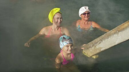 Baby girl, mom and grandmother in a swim in hot saline mineral water bath at a traditional spa outdoor with soft lighting and steam. Girls woman relax spring in hot geothermal spa pool is towel cap.