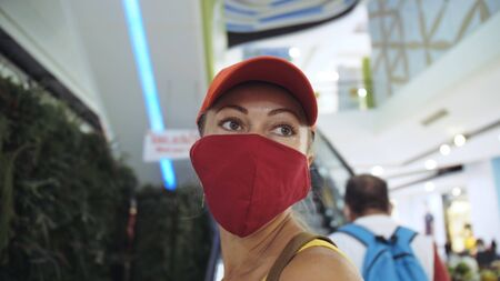 Woman travel caucasian visitor at a supermarket with wearing protective medical mask. Girl tourist customer a grocery store with protect respirator. Virus protection coronavirus pandemic covid-19. Stock fotó