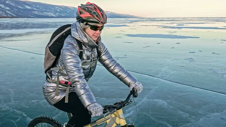 Woman is riding bicycle on the ice. Girl is dressed in a silvery down jacket, cycling backpack and helmet. Ice of the frozen Lake Baikal. Tires on bike are covered with spikes. Traveler is ride cycle. Reklamní fotografie