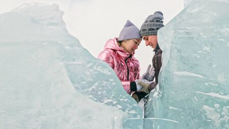 Couple has fun winter walk against background of ice of frozen lake. Lovers lie on clear ice with cracks have fun kiss and hug. View from above. Happy people on snow covered ice. Honeymoon love story. Imagens