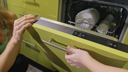 Mother teaching daughter smart girl learning to use dishwasher. Stylish modern Built In Kitchen Appliances in green black. Young mistress children loading putting dirty dishes in automatic dishwasher.