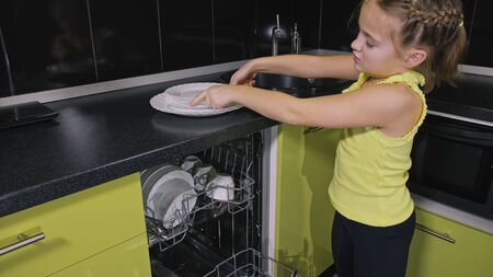 Smart girl learning to use dishwasher. Stylish modern Built In Kitchen Appliances in green black. Young mistress children study loading automatic electric dishwasher. Child is putting clean dishes.