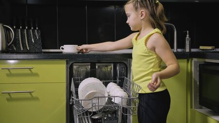 Smart girl learning to use dishwasher. Stylish modern Built In Kitchen Appliances in green black. Young mistress children study loading automatic electric dishwasher. Child is putting dirty dishes.