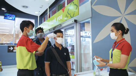 PATTAYA, THAILAND - MARCH 20, 2020: Temperature check at supermarket Big C, grocery store with a thermal imaging camera. Image monitoring scanner the body temperature of customer. Hand Sanitizer gel. Editoriali