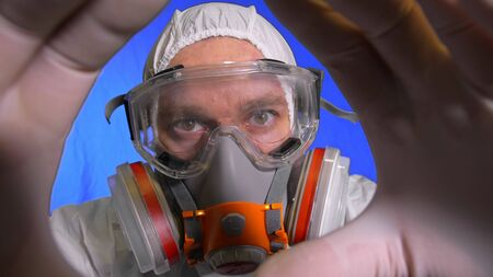 Scientist virologist in respirator. Slow motion. Man close up look, wearing protective medical mask. Concept health safety N1H1 virus protection coronavirus epidemic 2019 nCoV. Chroma key blue film.
