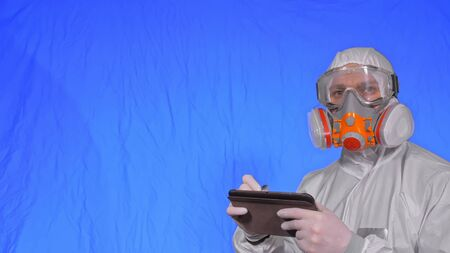 Scientist virologist in respirator makes write in an tablet computer with stylus. Man wearing protective medical mask. Concept health safety virus coronavirus epidemic 2019 nCoV. Chroma key blue.