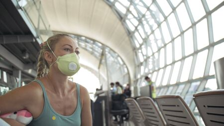 Woman caucasian at airport with wearing protective medical mask on head against the background of the plane. Concept health safety virus protection coronavirus epidemic sars-cov-2 covid-19 2019-ncov. Archivio Fotografico