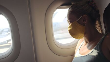 Woman travel caucasian at plane with wearing protective medical mask. Girl tourist at aircraft with protect respirator. Concept virus protection coronavirus epidemic sars-cov-2 covid-19 2019-ncov.