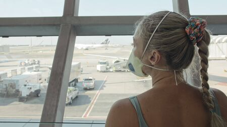 Woman caucasian at Suvarnabhumi Airport with wearing protective medical mask on head against background of plane. Concept health virus protection coronavirus epidemic sars-cov-2 covid-19 2019-ncov. Archivio Fotografico