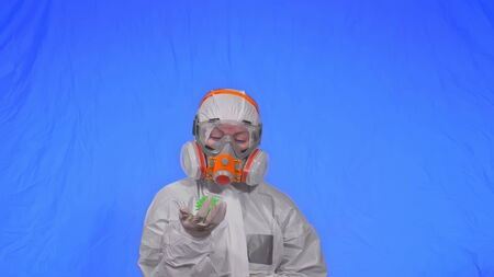 Doctor in respirator show a virus model concept health safety protection coronavirus epidemic 2019 nCoV. Slow motion. Woman wearing protect medical aerosol spray paint mask. Green ball spike thorn.