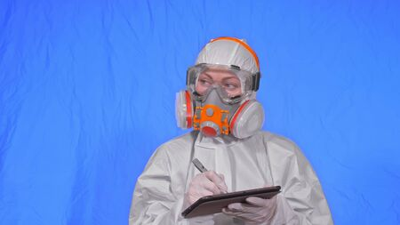 Scientist virologist in respirator makes write in an tablet computer with stylus. Woman wearing protective medical mask. Concept health safety virus coronavirus epidemic 2019 nCoV. Chroma key blue.