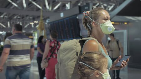 Woman and child baby tourist caucasian at airport with wearing protective medical mask. Family in quarantine isolation. Health safety virus protect coronavirus epidemic sars-cov-2 covid-19 2019-ncov.