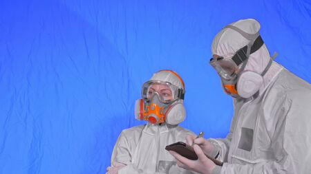 Scientist virologist in respirator makes write in an tablet computer with stylus. Man and woman wearing protective medical mask. Health safety virus coronavirus epidemic 2019 nCoV. Chroma key blue.