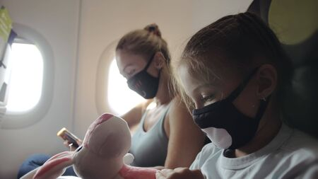 Family woman and child baby travel tourist caucasian at plane aircraft with wearing protective medical mask. Use smartphone mobile. Health virus protect coronavirus epidemic sars-cov-2 covid-19.