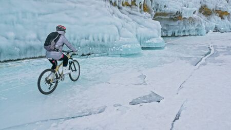 Woman is riding bicycle near the ice grotto. The rock with ice caves and icicles. Girl is dressed in silvery down jacket, cycling backpack and helmet. Tires winter with spikes. Traveler is ride cycle.