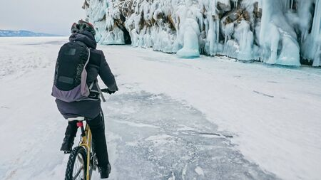 Man is riding bicycle near ice grotto. Rock with ice caves icicles. Teenage is dressed in black down jacket, cycling backpack, helmet. Tires on covered with special spikes. Traveler boy is ride cycle.