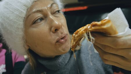 Girl eat pizza cheese four. Close up of young woman mouth greedily eating pizza and chewing in outdoor restaurant. Human hands taking pieces slices of hot tasty italian pizza from open box. Junk food. Imagens