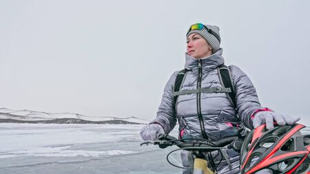 Woman stands near her bike on ice. The girl cyclist stopped to rest. The beautiful view of the sunset. The traveler is ride a cycle. Female is riding bike on the ice. Athlete puts on gear.