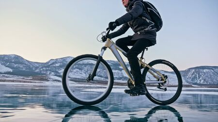 Man is riding bicycle on the ice. Ice of the frozen Lake Baikal. Teenage is dressed in black down jacket, cycling backpack, helmet. Tires on covered with special spikes. Traveler boy is ride cycle.