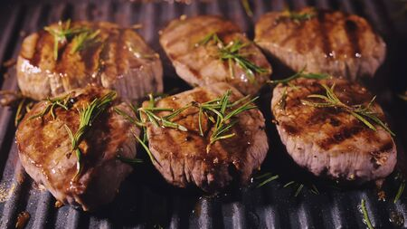 Delicious juicy meat steak cooking on grill. Aged prime rare roast grilling tenderloin fresh marble tenderness beef. Prime beef fry on electric roaster, rosemary, black pepper, salt. Slow motion.