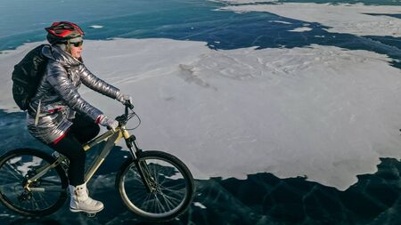 Woman is riding bicycle on the ice. Girl is dressed in a silvery down jacket, cycling backpack and helmet. Ice of the frozen Lake Baikal. Tires on bike are covered with spikes. Traveler is ride cycle. Imagens