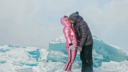 Couple has fun winter walk against background of ice of frozen lake. Lovers lie on clear ice with cracks have fun kiss and hug. View from above. Happy people on snow covered ice. Honeymoon love story.