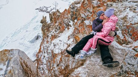 Couple enjoying walking outdoors in winter top mountains. Active couple walking on through snow together winter time beautiful winter sunny day. Couple of hiker walk on trail among snow covered hill.