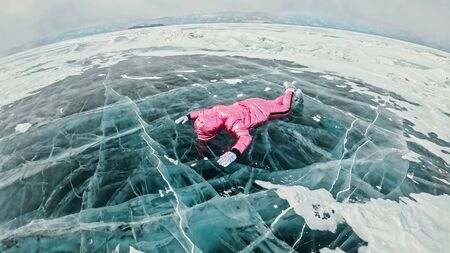 Girl walking on cracked ice of frozen lake Baikal. Woman traveler explores and looks at an ice floe. Magic purest place in nature. Ice arounds traveler all his trip. Hiker walk in cosmic pink jacket.