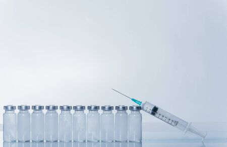 Medicine, Injection, vaccine and disposable syringe, drug concept. Sterile vial medical syringe needle. Macro close up. Glass medical ampoule vial for injection. Bottles ampule with aluminum cap. Imagens