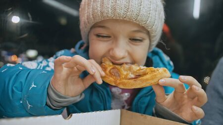 Child eat pizza cheese four. Close up of young girl woman mouth greedily eating pizza and chewing in outdoor restaurant. Kid children hands taking piece slice of hot tasty italian pizza from open box. Imagens