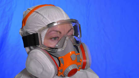 Scientist virologist in respirator. Slow motion. Woman close up look wearing protective medical mask. Concept health safety N1H1 virus protection coronavirus epidemic 2019 nCoV. Chroma key blue film. 免版税图像