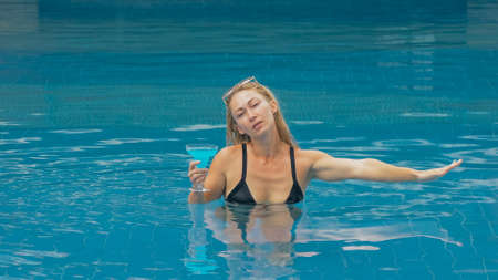 Middle shot pretty woman drinking blue cocktail alcohol liquor in swimming pool at hotel. Portrait of sexy girl in pool outdoor. Beautiful caucasian women with blond hair, black swimsuit, sunglasses.