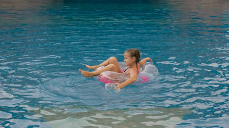 The little cute girl have fun in the swim pool. The child enjoy summer vacation in a swimming pool jumping, spinning, splash water. Slow motion. Happy childhood.