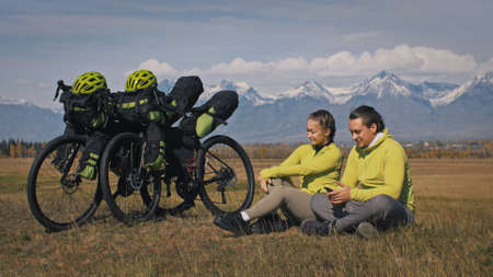 The man and woman travel on mixed terrain cycle touring with bikepacking. The two people journey with bicycle bags. Sport bikepacking, bike, sportswear in green black colors. Mountain snow capped.