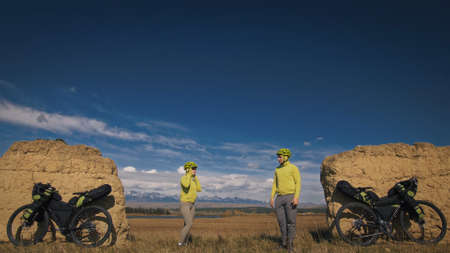 The man and woman travel on mixed terrain cycle bike touring with bikepacking. The two people journey with bicycle bags. Sport sportswear in green black colors. Mountain snow capped, stone arch. Foto de archivo