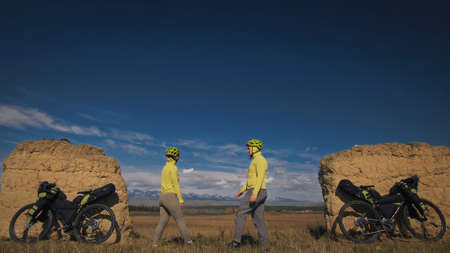 The man and woman travel on mixed terrain cycle bike touring with bikepacking. The two people journey with bicycle bags. Sport sportswear in green black colors. Mountain snow capped, stone arch.