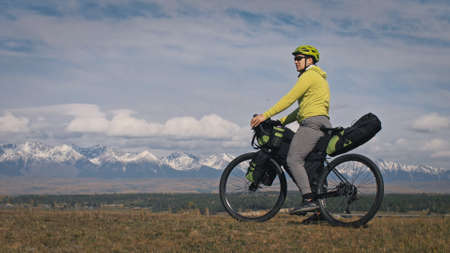 The man travel on mixed terrain cycle touring with bikepacking. The traveler journey with bicycle bags. Sport tourism bikepacking, bike, sportswear in green black colors. Mountain snow capped.