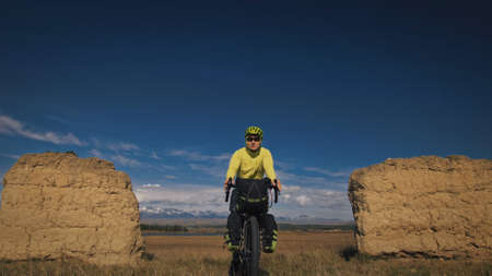 The man travel on mixed terrain cycle touring with bikepacking. The traveler journey with bicycle bags. Sport bikepacking, bike, sportswear in green black colors. Mountain snow capped, stone arch.