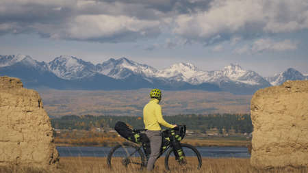 The man travel on mixed terrain cycle touring with bikepacking. The traveler journey with bicycle bags. Sport bikepacking, bike, sportswear in green black colors. Mountain snow capped, stone arch. Stock Photo