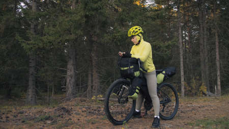 The woman travel on mixed terrain cycle touring with bike bikepacking outdoor. The traveler journey with bicycle bags. Sportswear in green black colors. Magic forest park. Make a selfie smartphone.