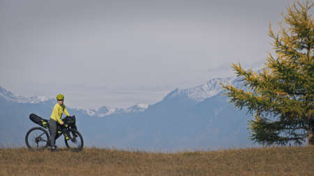 The woman travel on mixed terrain cycle touring with bikepacking. The traveler journey with bicycle bags. Sport tourism bikepacking, bike, sportswear in green black colors. Mountain snow capped. 版權商用圖片