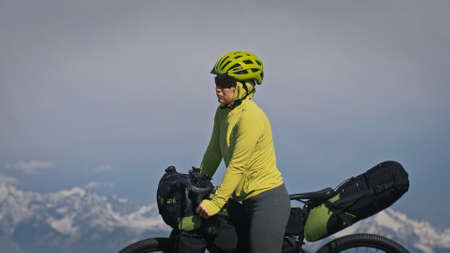 The woman travel on mixed terrain cycle touring with bikepacking. The traveler journey with bicycle bags. Sport tourism bikepacking, bike, sportswear in green black colors. Mountain snow capped. Foto de archivo